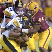 Arizona State linebacker Dale Robinson wraps up Iowa running back Jermille Lewis at Sun Devil Stadium, on Sept. 18, 2004.