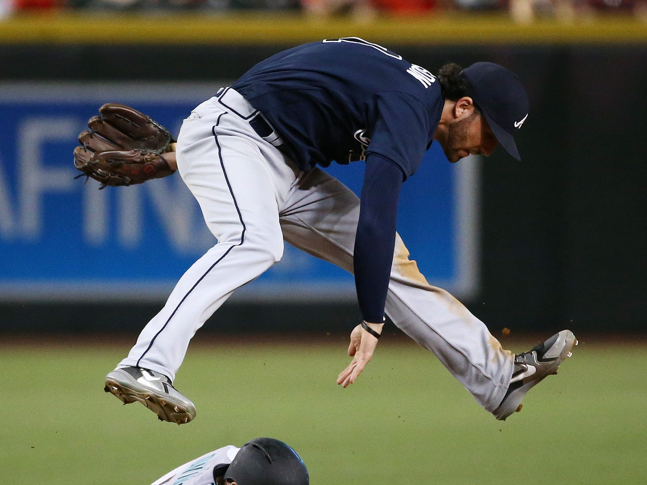 Arizona Diamondbacks Chris Owings slides into second base as Atlanta Braves Dansby Swanson turns the double play to end the seventh inning on Sep. 6, 2018, at Chase Field in Phoenix, Ariz.