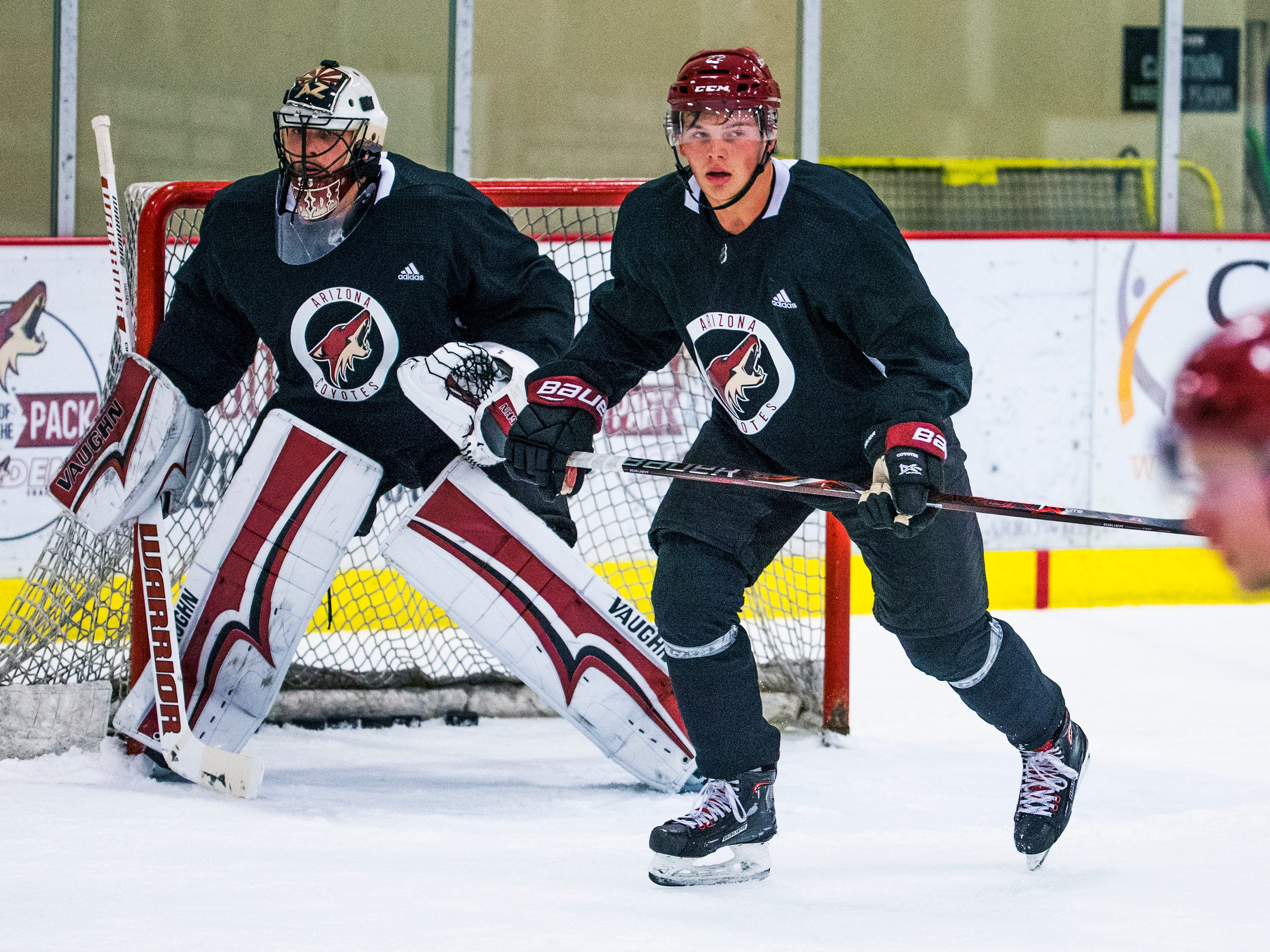 Barrett Hayton, middle, skates in front of the goal during Arizona Coyotes rookie camp at Ice Den Scottsdale, Friday, September 7, 2018.