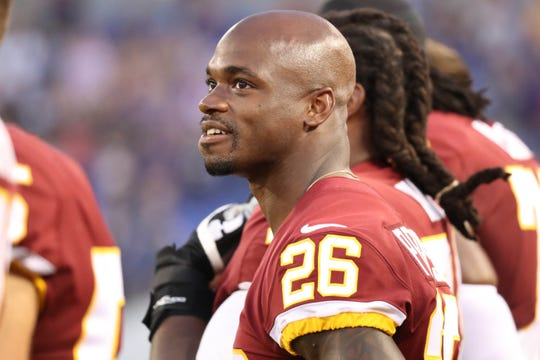 Redskins running back Adrian Peterson (26) watches the scoreboard during the national anthem prior to a game against the Ravens.