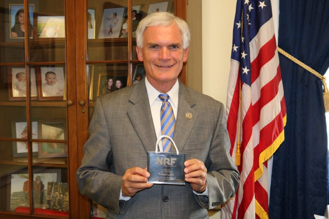 """U.S. Rep. Bob Latta holds a """"Hero of Main Street"""" award presented to him by the National Retail Federation."""