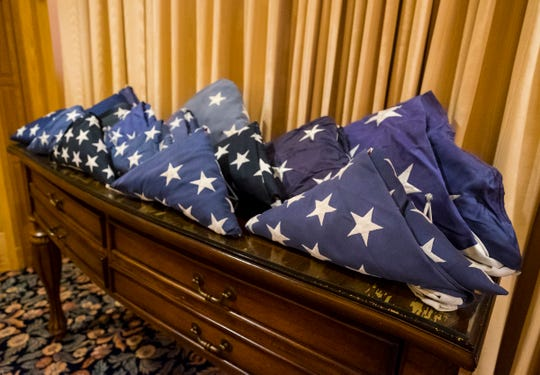 Retired American flags of different sizes are folded on top of a chest in the Pollock-Randall Funeral Home in Port Huron. The funeral home is collecting retired American flags to be cremated with veterans.