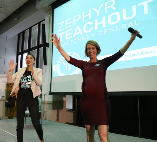 Alexandria Ocasio Cortez and Zephyr Teachout cheer the crowd during a rally for Teachout's campaign for attorney general at SUNY New Paltz on September 7, 2018.