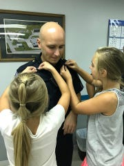 Hellam Township Police Lt. Drew Heistand's daughters pin his lieutenant's bars onto his uniform during his promotion on Sept. 6, 2018.
