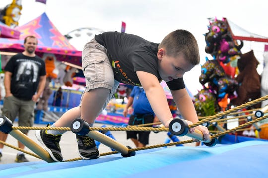 Wyatt Zechman from Mifflinberg tries to conquer the ladder climbing game at the 2018 York Fair.