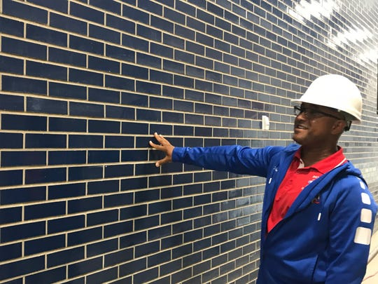 Monroe High assistant principal and varsity football coach Jason Muhammad describes the color of a newly built interior wall of the school.