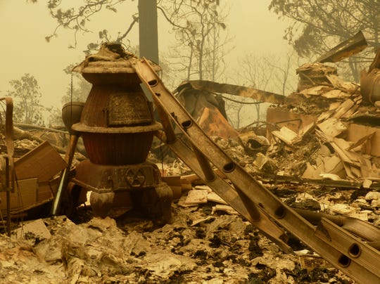 A pot-bellied stove sits in the rubble of a Pollard Flat home destroyed in the Delta Fire.