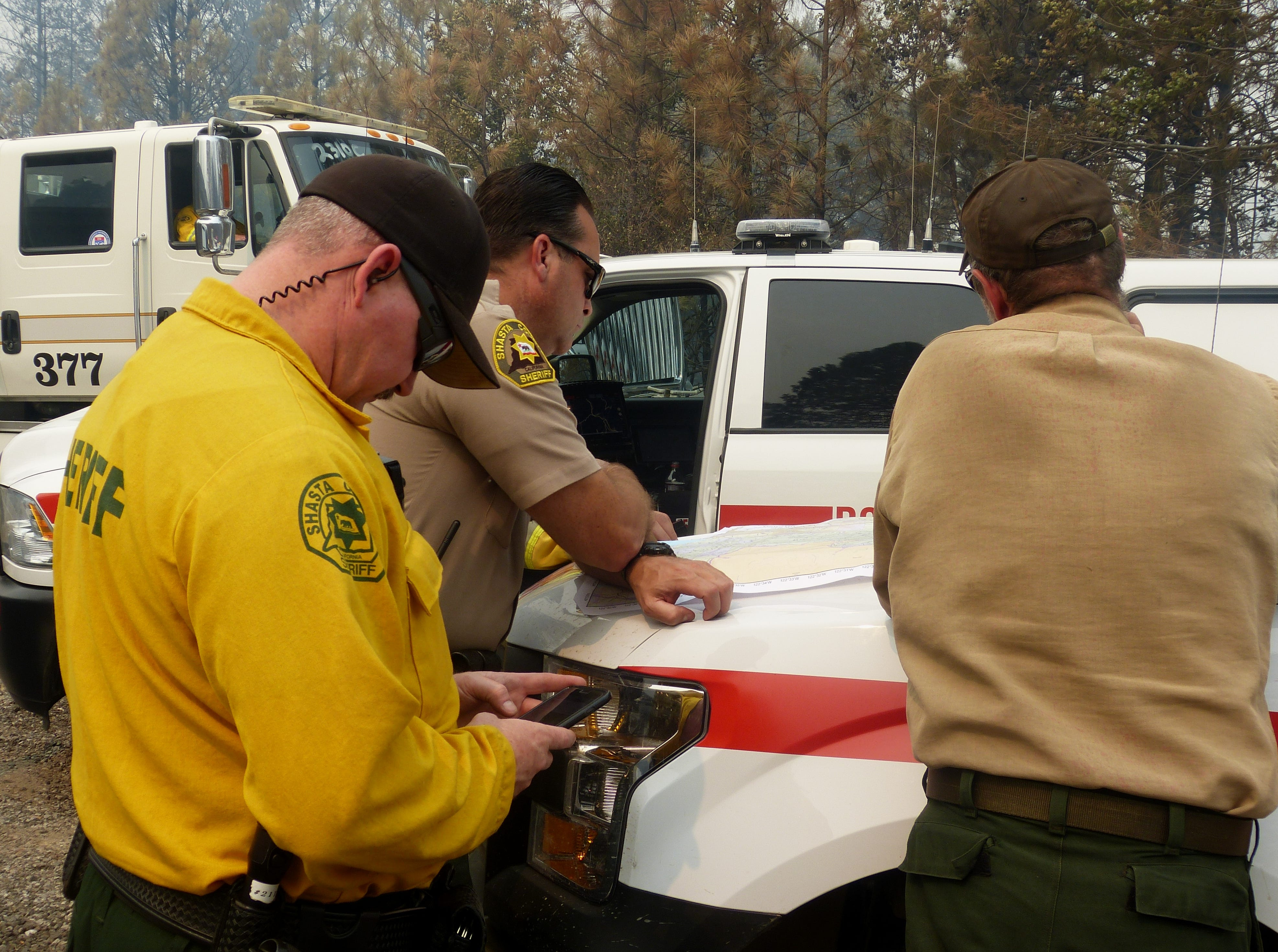 Firefighters, sheriff's personnel and others study an operations map for the Delta Fire Friday.