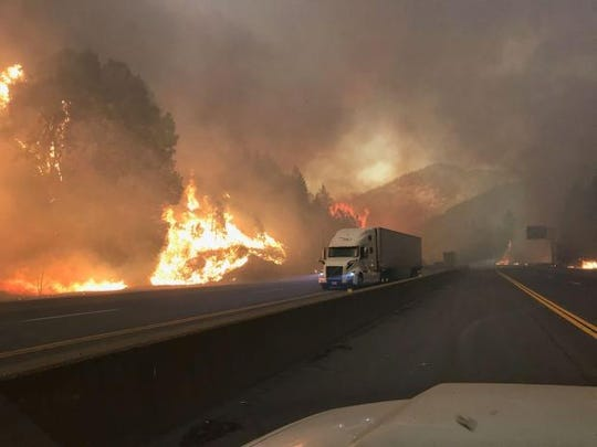 A big rig on Interstate 5 passes on Wednesday, Sept. 5, 2018 a wall of flames from the Delta Fire.