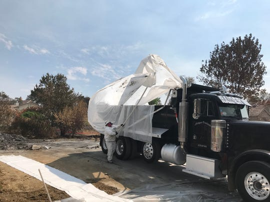 """Burrito wrapping"" a dump truck filled with debris collected from a Redding home destroyed in the Carr Fire. The plastic overwrap prevents ashes and debris from flying out as the load is driven to a landfill in Anderson."