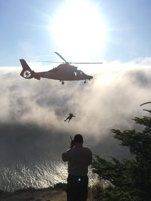 A Coast Guard helicopter and rescue teams conduct a rescue operation at God's Thumb north of Lincoln City earlier this year.