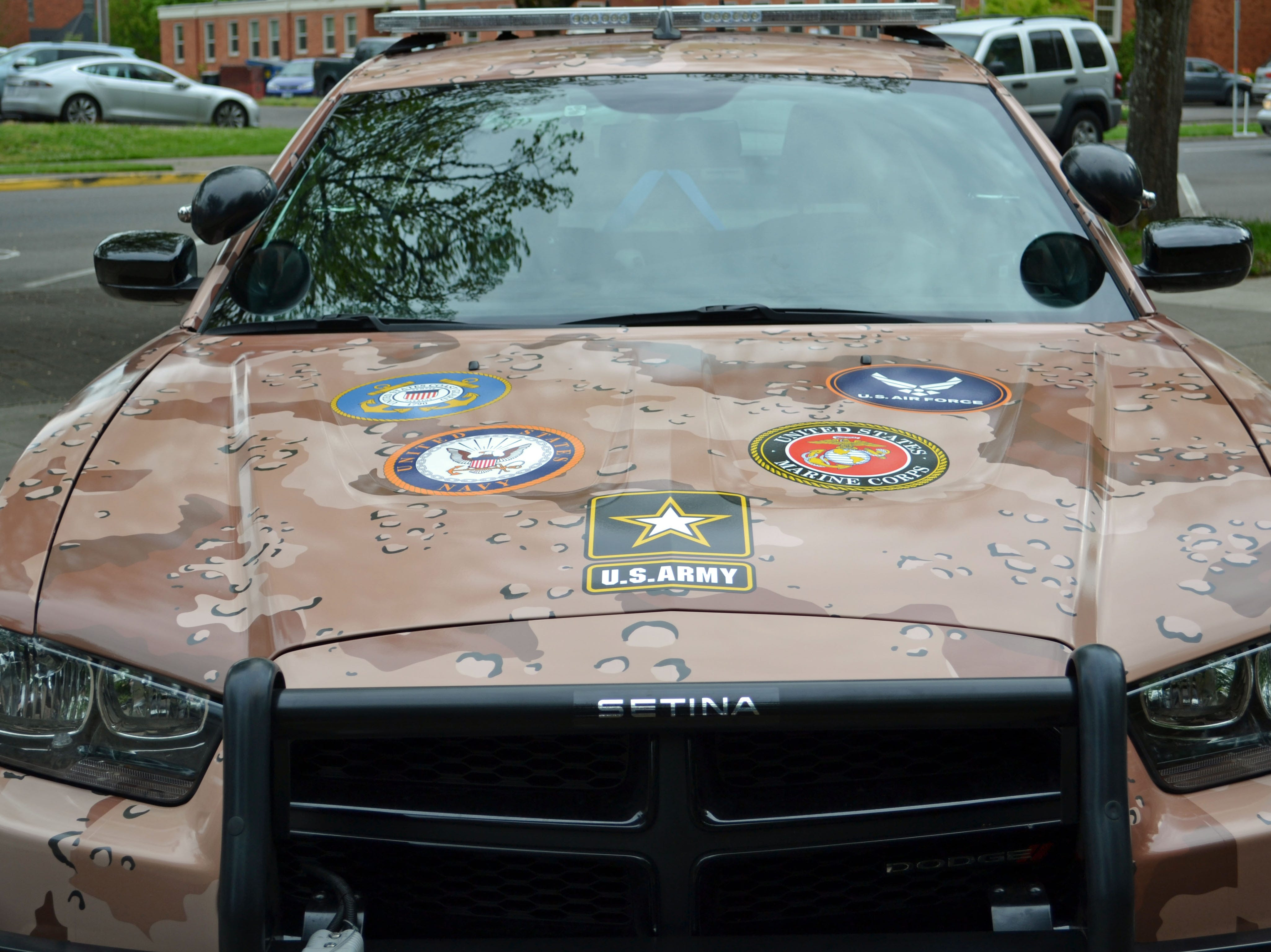 Logos from all military branches are displayed on a custom camouflage wrap  on a Salem Police Department for National Military Appreciation Month in May of 2017.