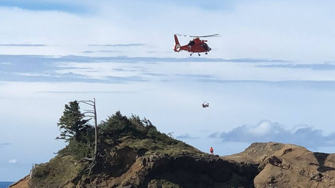 A Coast Guard helicopter and rescue teams conduct a rescue operation at God's Thumb north of Lincoln City .
