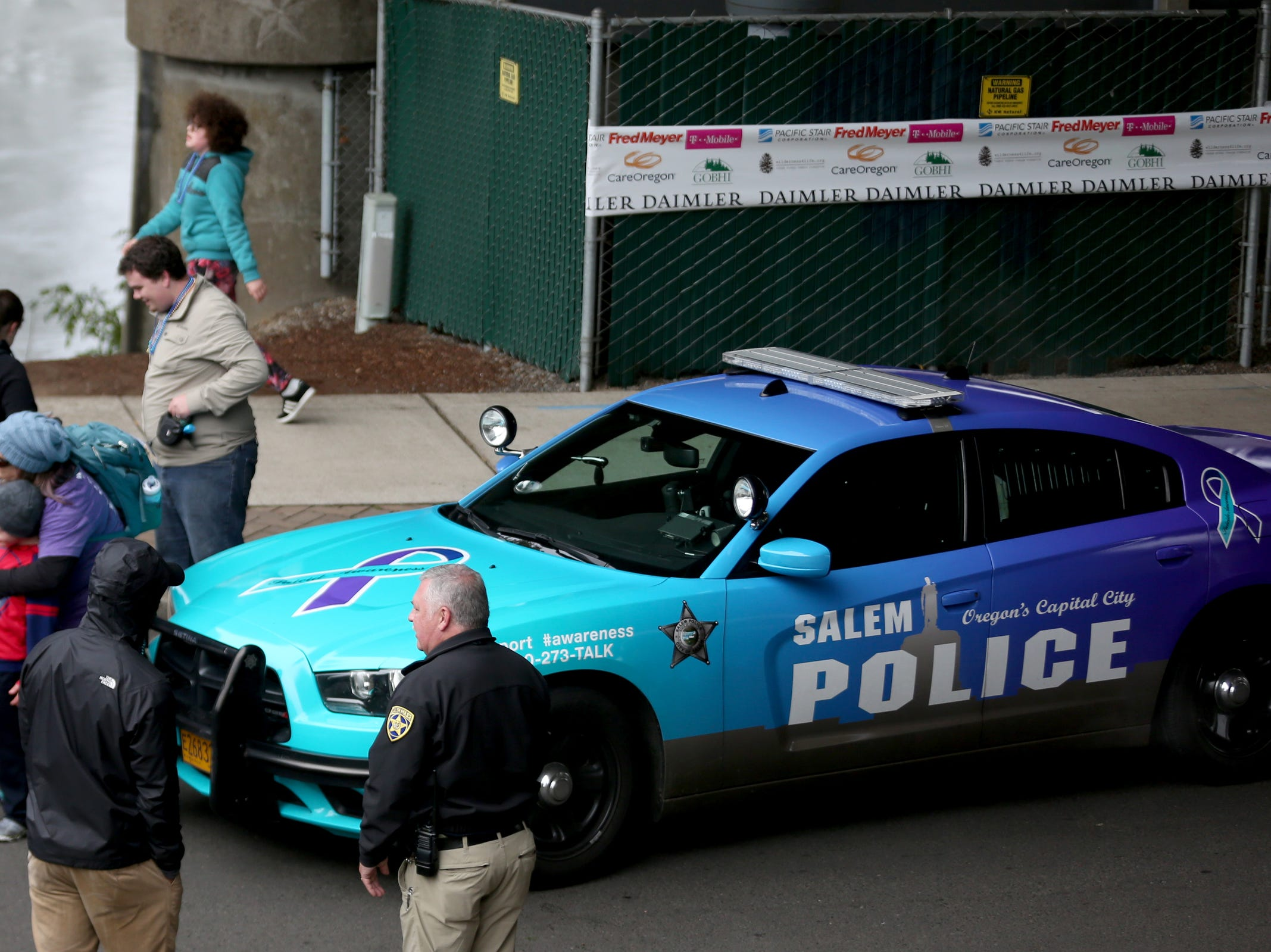 A Salem Police car wrapped in turquoise and purple to raise awareness for suicide prevention during the Out of the Darkness walk at Riverfront Park in Salem on Saturday, Oct. 14, 2017.