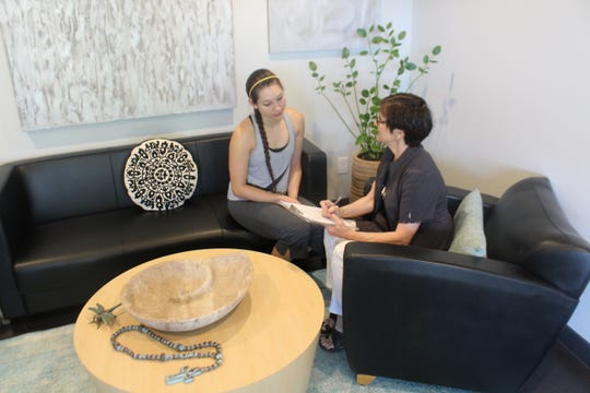 Owner Jody White and patient Jamie Meeks filling out paperwork in the lobby of  Jody Aesthetics, 2102 Pecos St., suite 12.