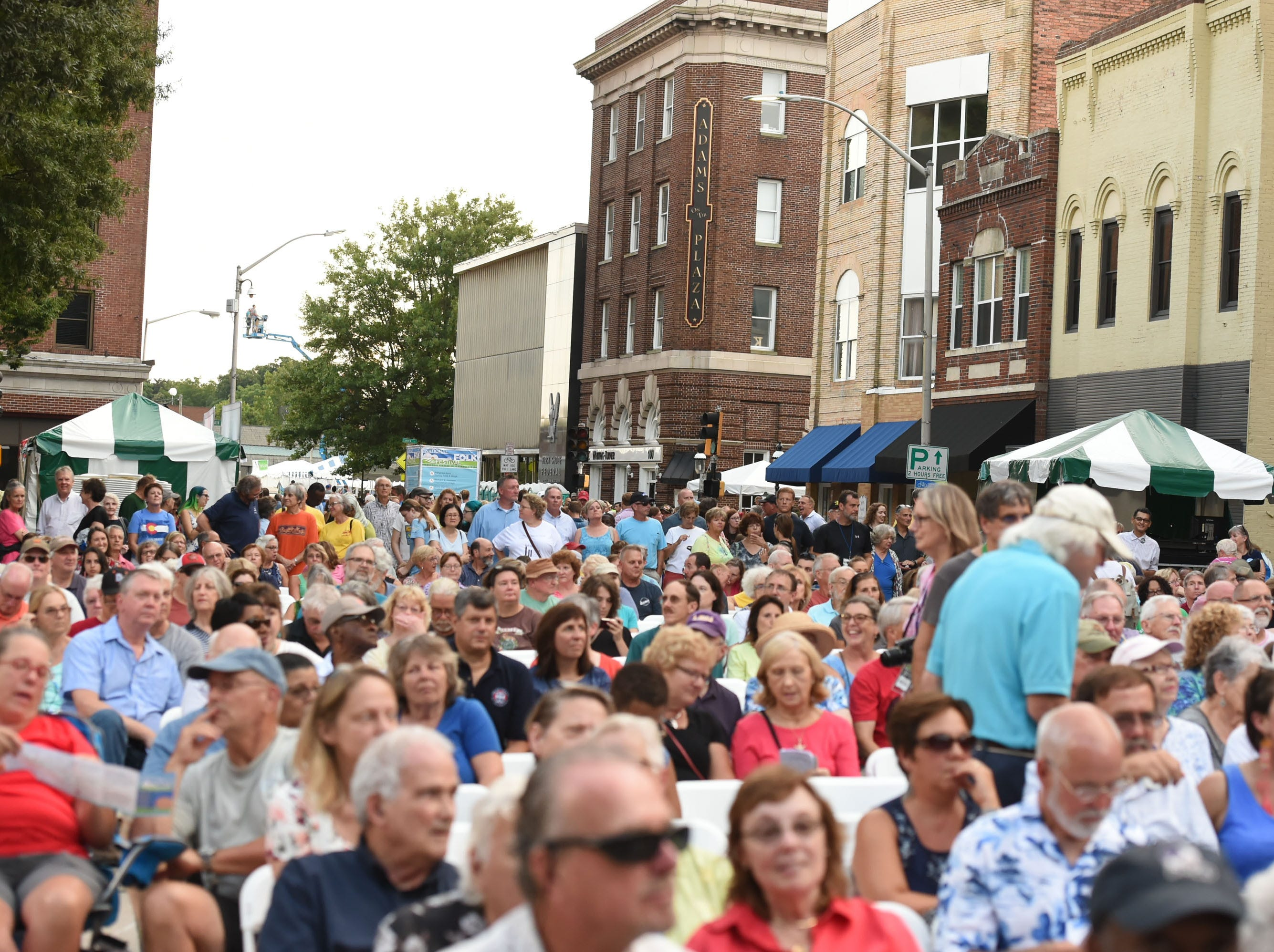 A large crowd fills South Division Street during the kick off of the 78th National Folk Festival on Friday, Sept. 7, 2018.