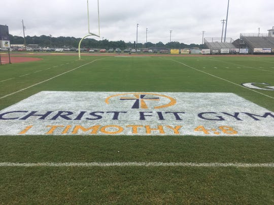 Christ Fit Gym's advertisement is pictured painted on the football field at Benton High School prior to being removed.