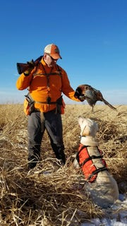 John Pollmann bags a bird with the help of his hunting companion, Buddy.