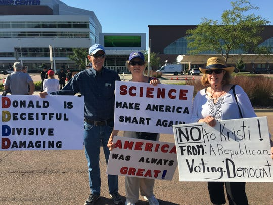 Pete Hesla, 72, Ann Hesla, 69, both of Hudson, South Dakota, and Jude Fullenkamp, 70, of Hartford, show signs of protest at the closed event fundraiser President Donald Trump spoke at in support of Kristi Noem Friday, Sept. 7, 2018, in Sioux Falls, SD.