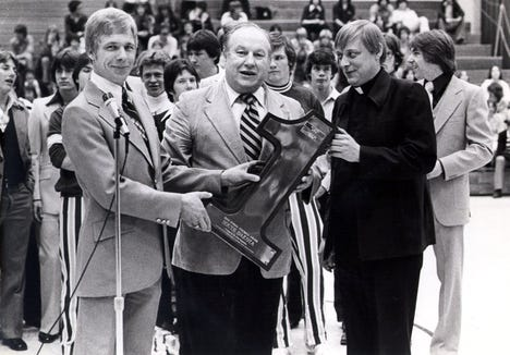 Legendary Sioux Falls football coach Bob Burns accepts a state championship trophy at O'Gorman, where he returned to the sideline in 1976 after a break from coaching.