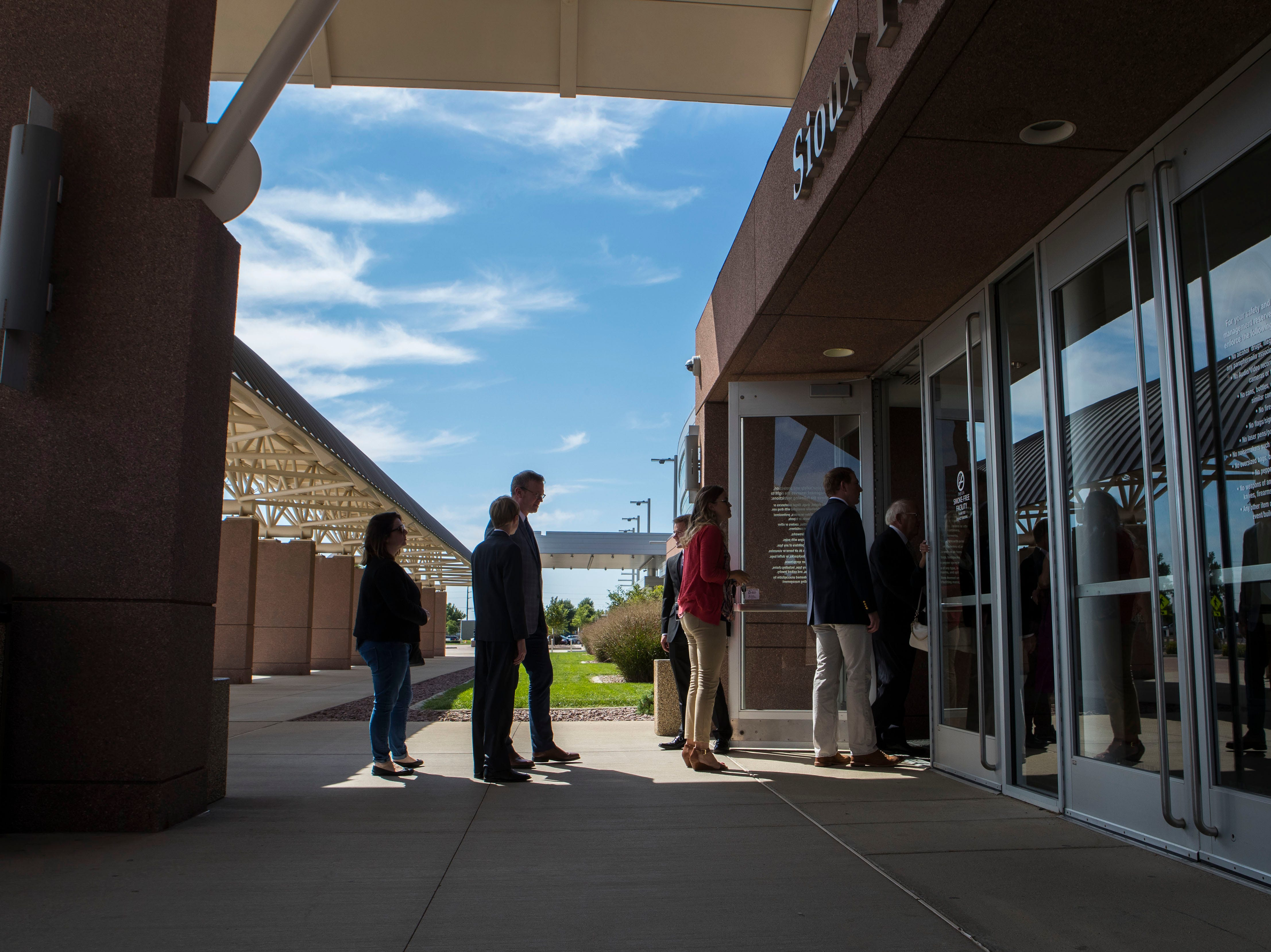 People stand in line at the Sioux Falls Convention Center for the closed-door fundraiser where President Donald Trump will be attending in support of Republican gubernatorial hopeful Kristi Noem on Friday, Sept. 7, 2018 in Sioux Falls, S.D.