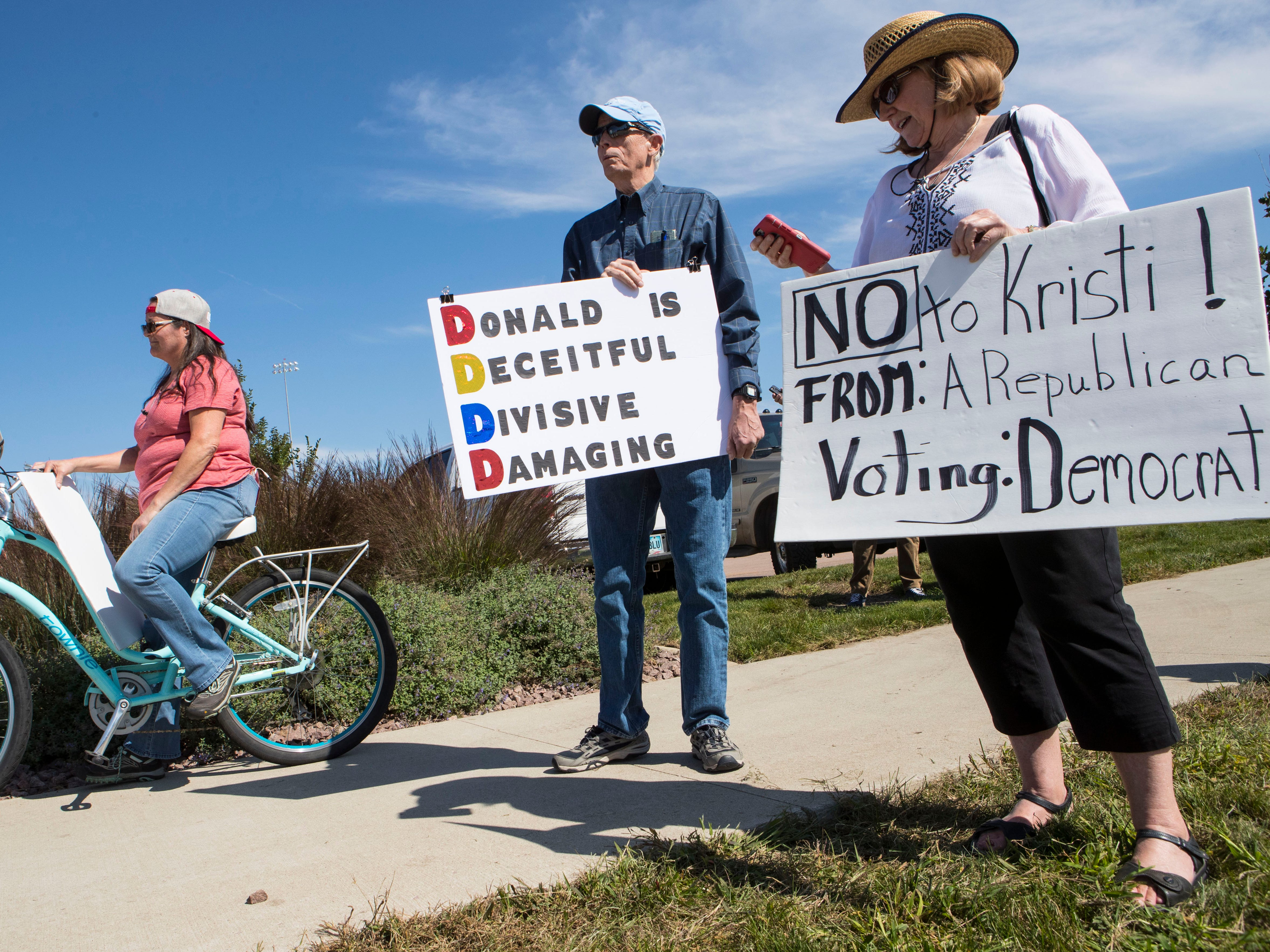 Protesters stand outside of the Denny Sanford Premier Center where President Donald Trump is attending a closed-door fundraiser for Republican gubernatorial hopeful Kristi Noem on Friday, Sept. 7, 2018 in Sioux Falls, S.D.