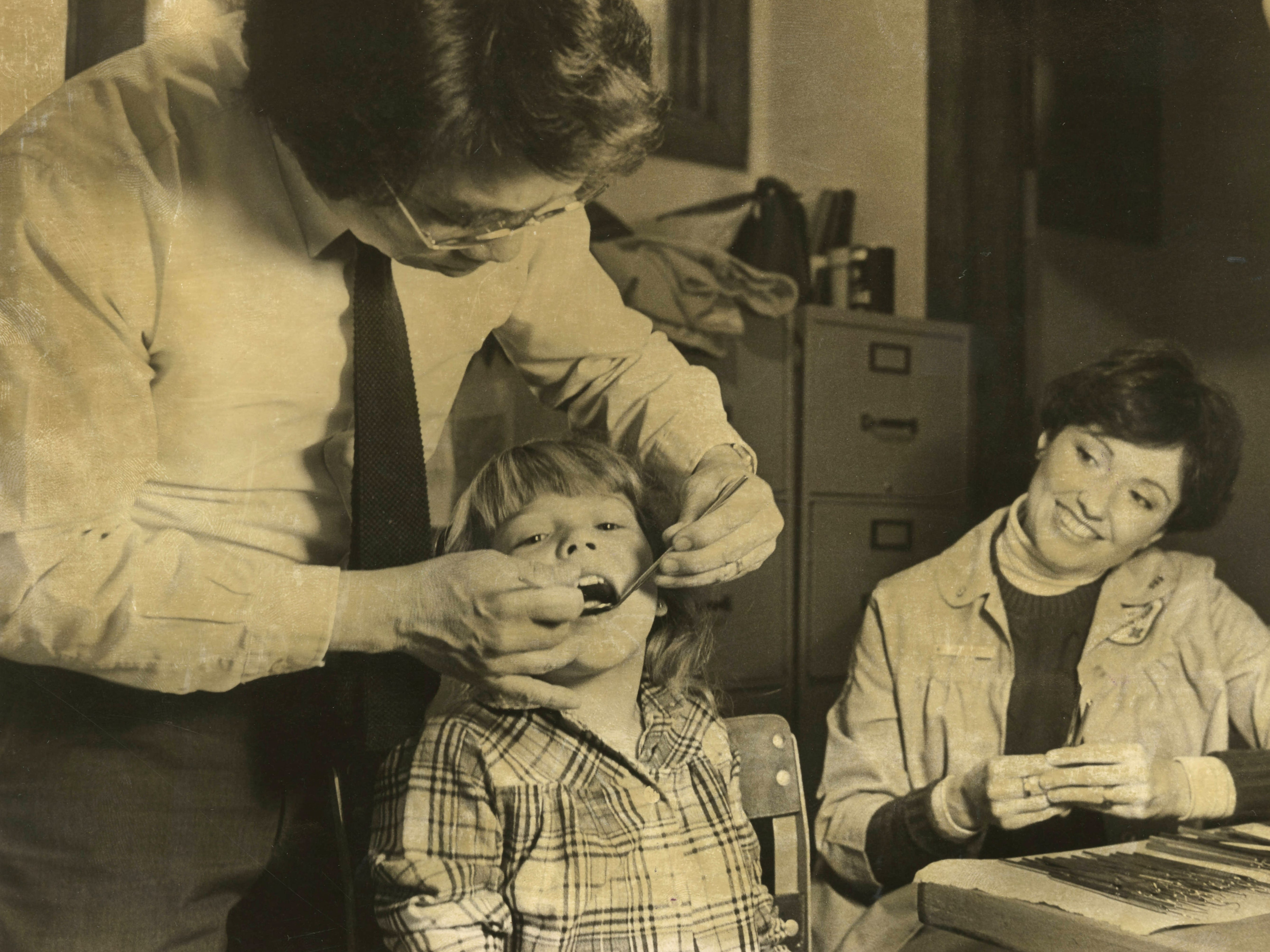 Dr. K.L. Young checked Tonya Brewer's teeth at Boyd Elementary School, as volunteer assistant Carol Noble watched in 1983.