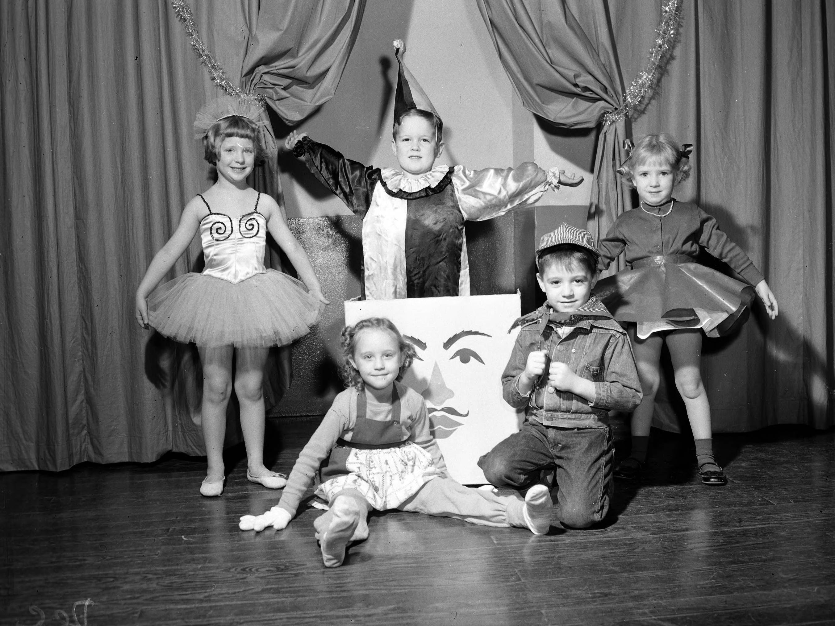Boyd Kindergarten Toy Shop play. Pictured are Carolyn Spencer as Raggedy Ann, Bruce Hinchey as a train engineer, Julie Wright as a walking ballet doll, Ronnie Murphy as the Jack-in-the-box, and Barbara Troutman as the skating doll. Published in the News & Leader on December 12, 1954.
