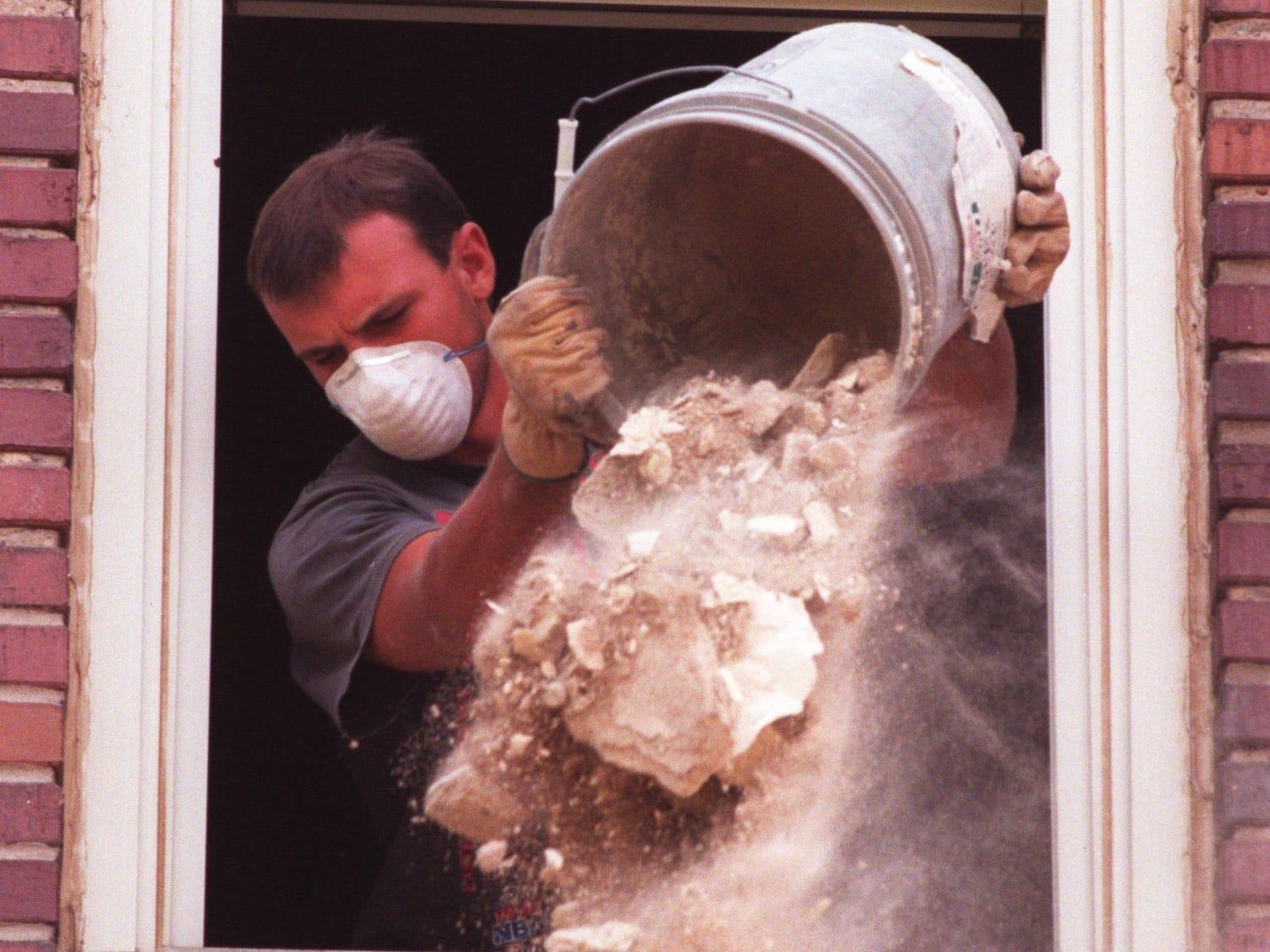 Richard Teague dumps a bucket of broken plaster at Boyd Elementary.
