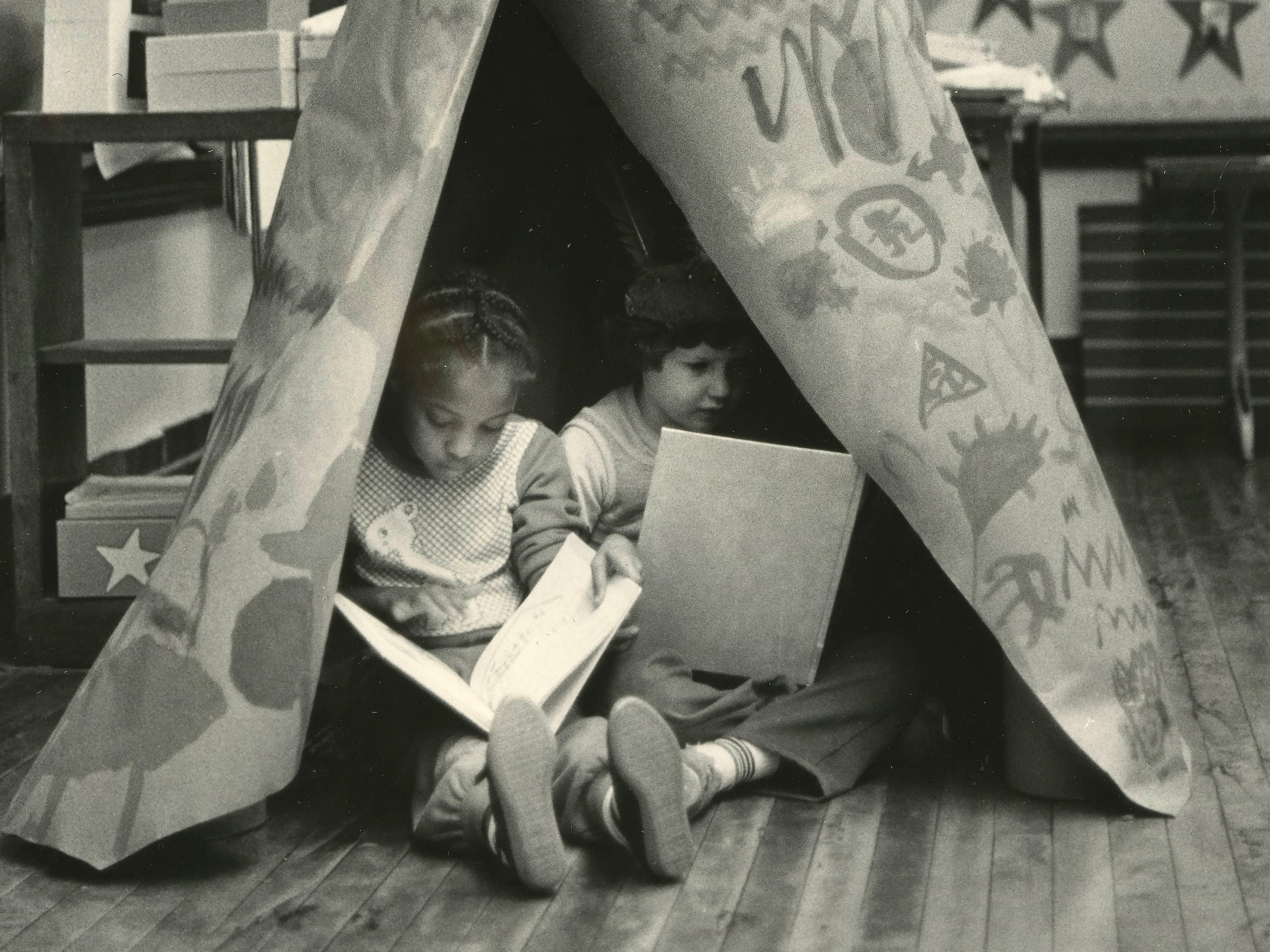 Kirstin King and Adam Letterman reading in a tepee constructed in their school room during studies about Thanksgiving at Boyd School in 1985.