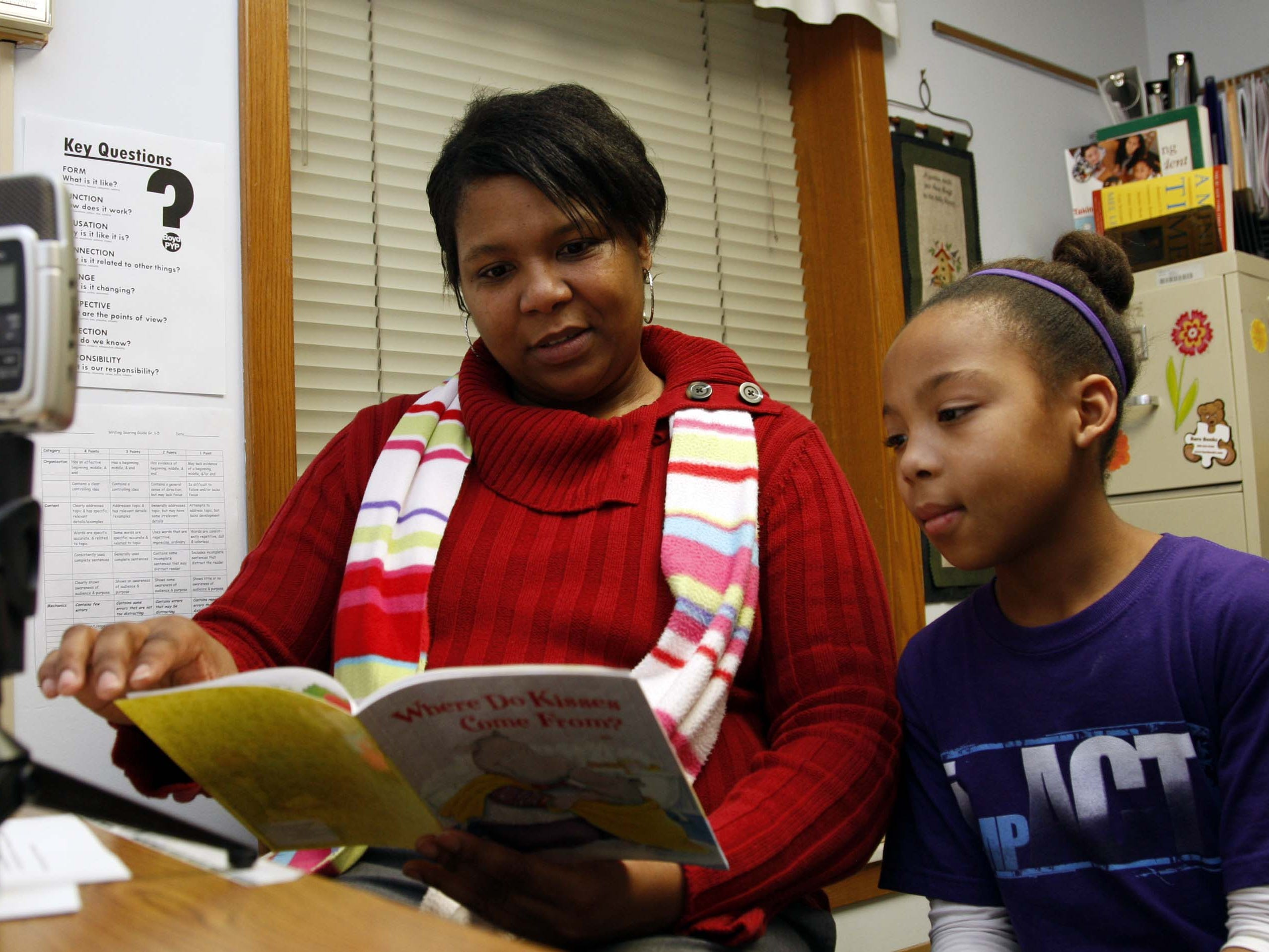 Kim Tucker sits with her daughter Kiara during a recorded reading session at Boyd Elementary.