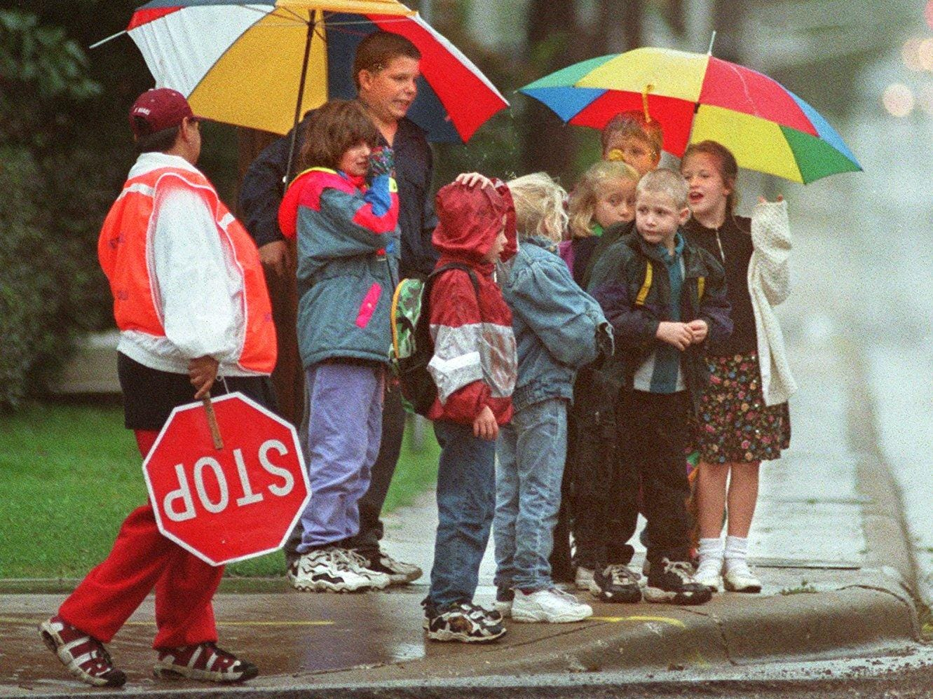 Schoolchildren try to stay dry at the corner of Washington and Division streets while waiting to cross after getting out of school at Boyd Elementary.