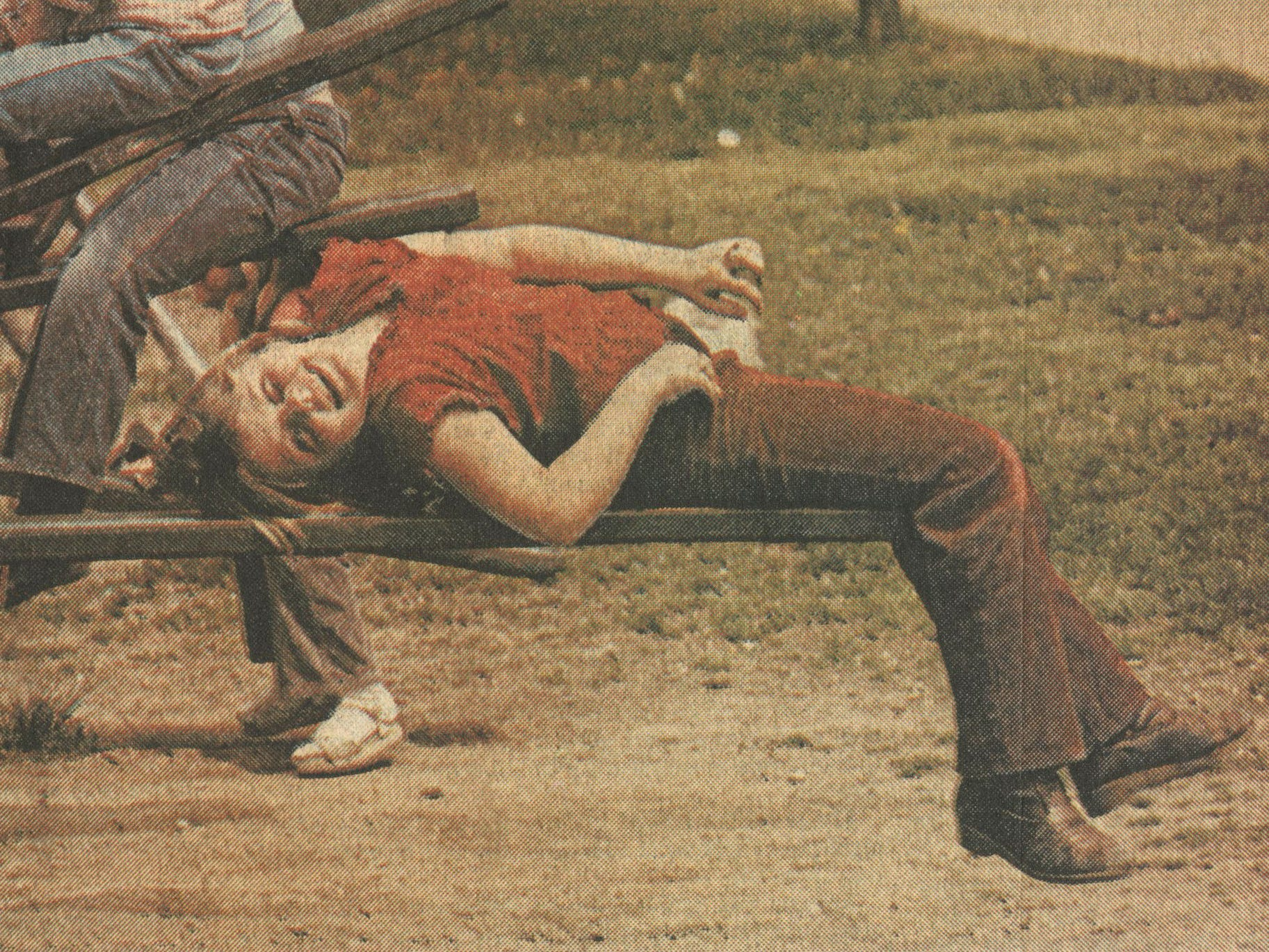 Julie Wharton, a third-grader at Boyd Elementary School, looks at the world from a different angle as she relaxes upside-down on a teeter-totter during recess in 1984.