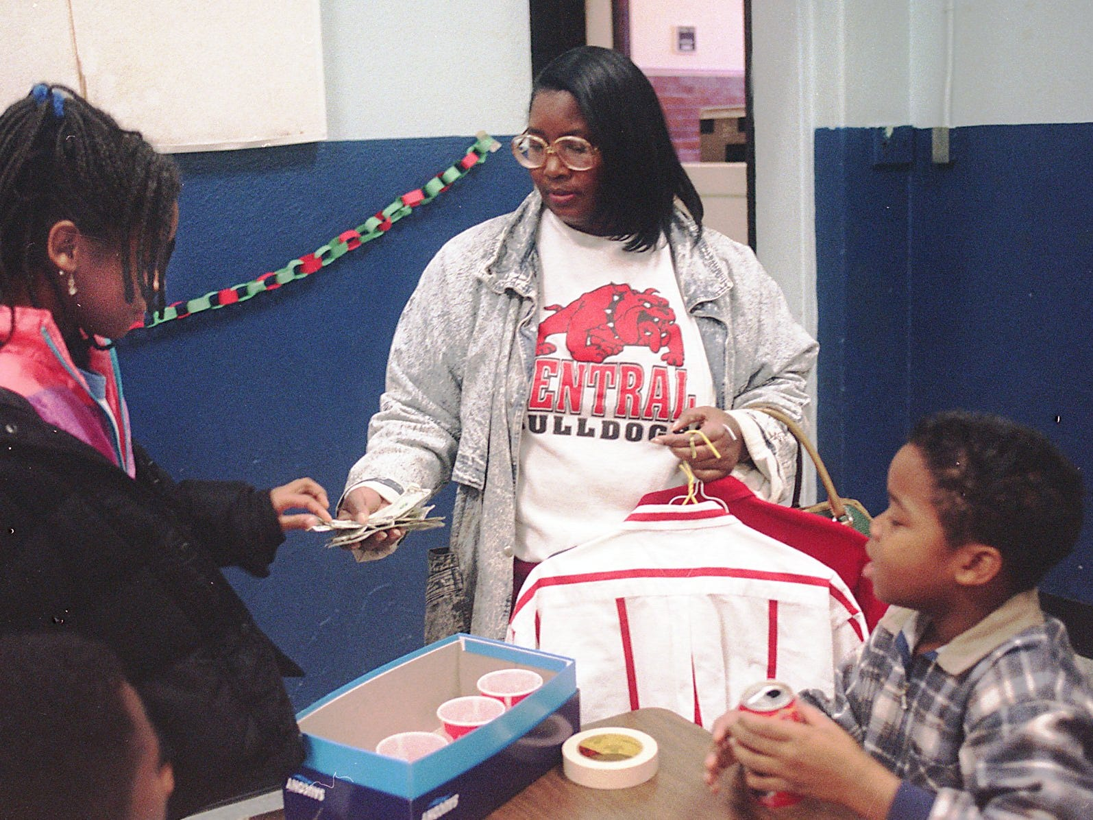 Boyd Elementary teacher Maxine Smith checks out and pays money to fourth-grader Danielle Foster while Dumone Starks watches.