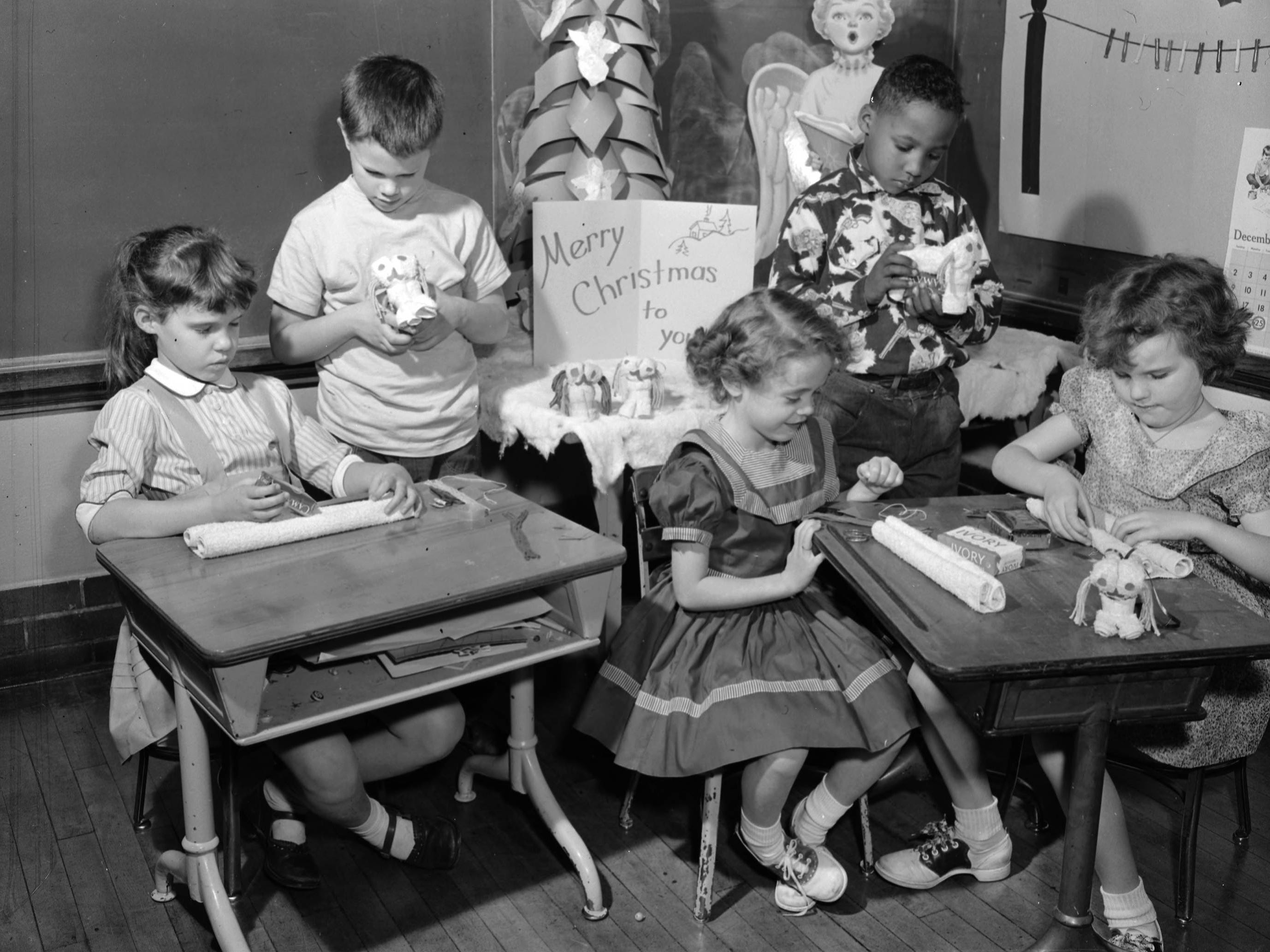 A group of first- and second-grade students in Mrs. Ruth Miller's class at Boyd School. They are creating Christmas presents for their parents. Pictured from left to right are Pam Abbott, Hayden Brunton, Judy Edmonds, Darrell Hutchison, and Georgene Rice. Published in the Leader & Press on Dec. 13, 1956.