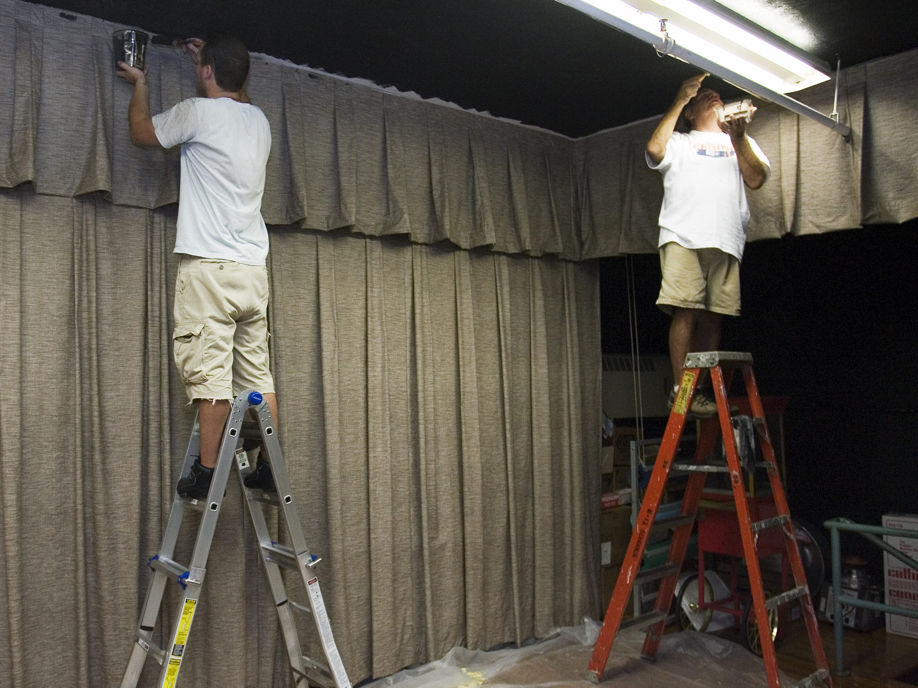 Boyd Allen (left) and Norman Kirsch, both with ESC Inc., paint the ceiling of the stage at Boyd Elementary on Thursday, Aug. 19, 2010. Allen and Kirsch were taking part in the 18th Annual Day of Caring.