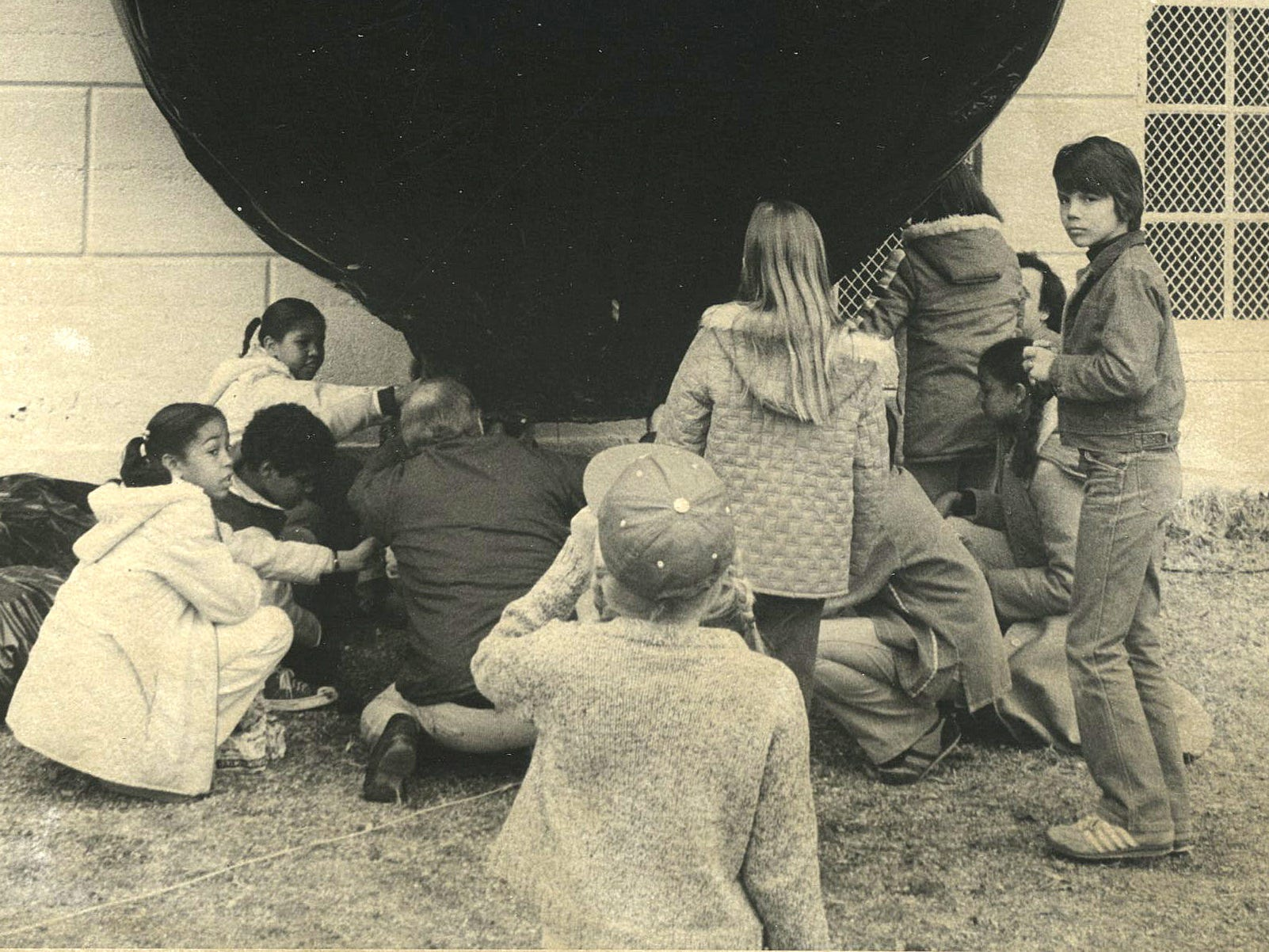 Students at Boyd Elementary School take the final step - building a fire to heat the air - in launching a hot air balloon constructed by pupils in 1979.