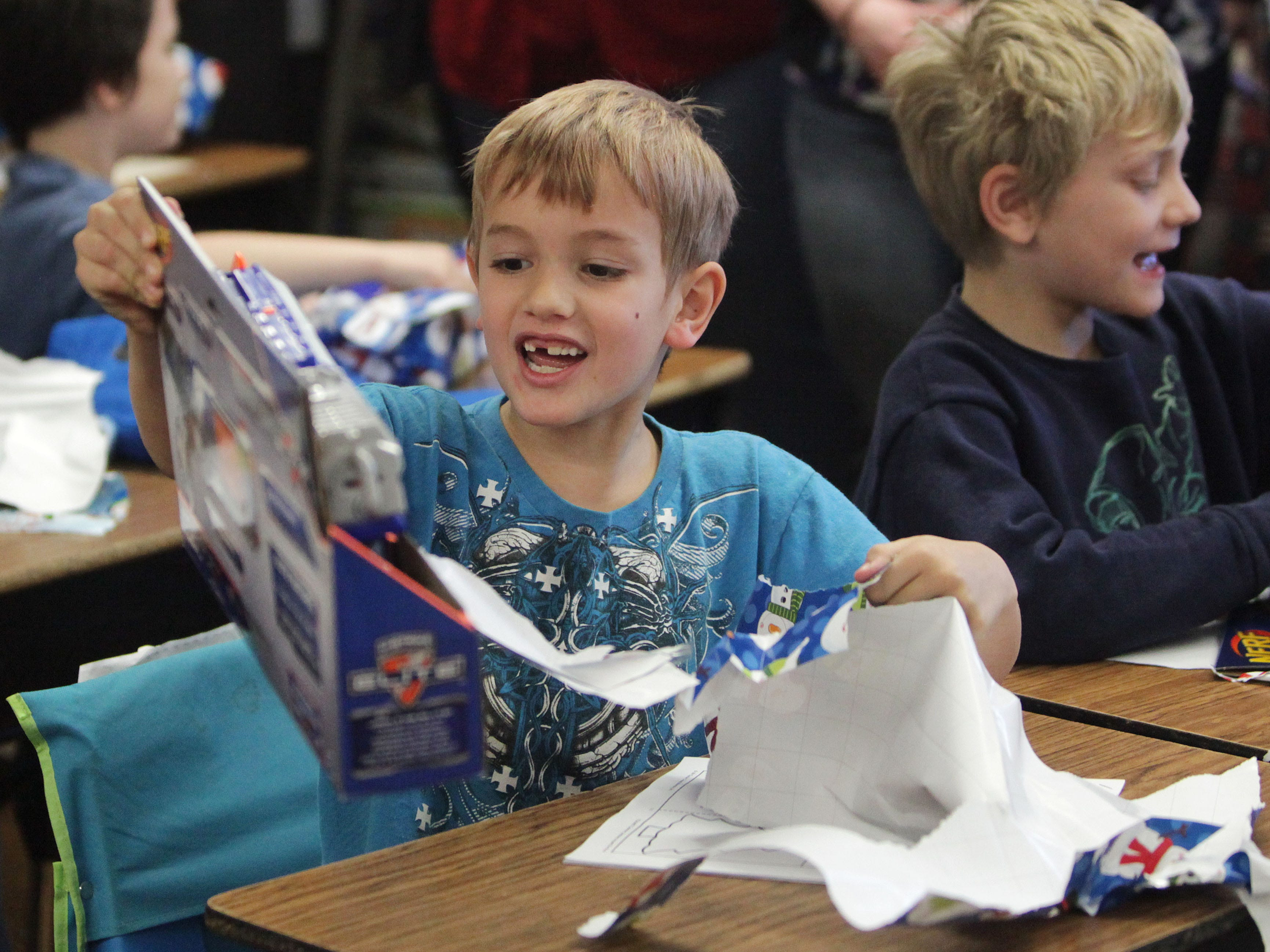 Harrison Adcock opens a present provided by CU Credit Union employees at Boyd Elementary on Wednesday, December 18, 2013.