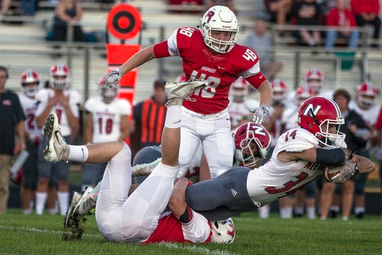 Lincoln's Caleb O'Neil tackles Neenah's Kaden Fritsch as Tyler Baldauf looks on during a football game between Wisconsin Rapids Lincoln and Neenah High School in Wisconsin Rapids, Wis., September 6, 2018.
