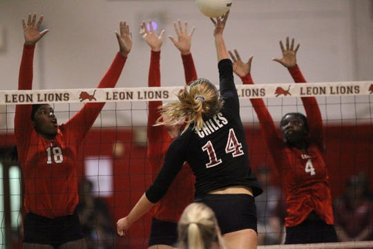 Chiles' Aly Freeland tries to tip over the Leon blockers Cailin Demps, Macy Maxwell and Shania Cromartie as Leon beat Chiles 3-0 on Thursday night in a District 2-8A volleyball game.