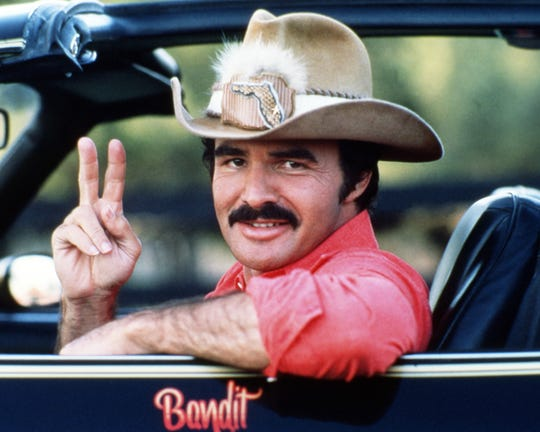 "Burt Reynolds is seen behind the wheel of his iconic Trans Am in ""Smokey and the Bandit"" (1977)."