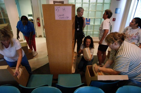 Employees from the Gifford Health Center pack up medical records from an overstuffed shelf so they can be moved into the new building across the street in October 2003, in Gifford. The new facility, located west of the Gifford Middle School on 28th Court, opened for patients in 2003 at the current location.