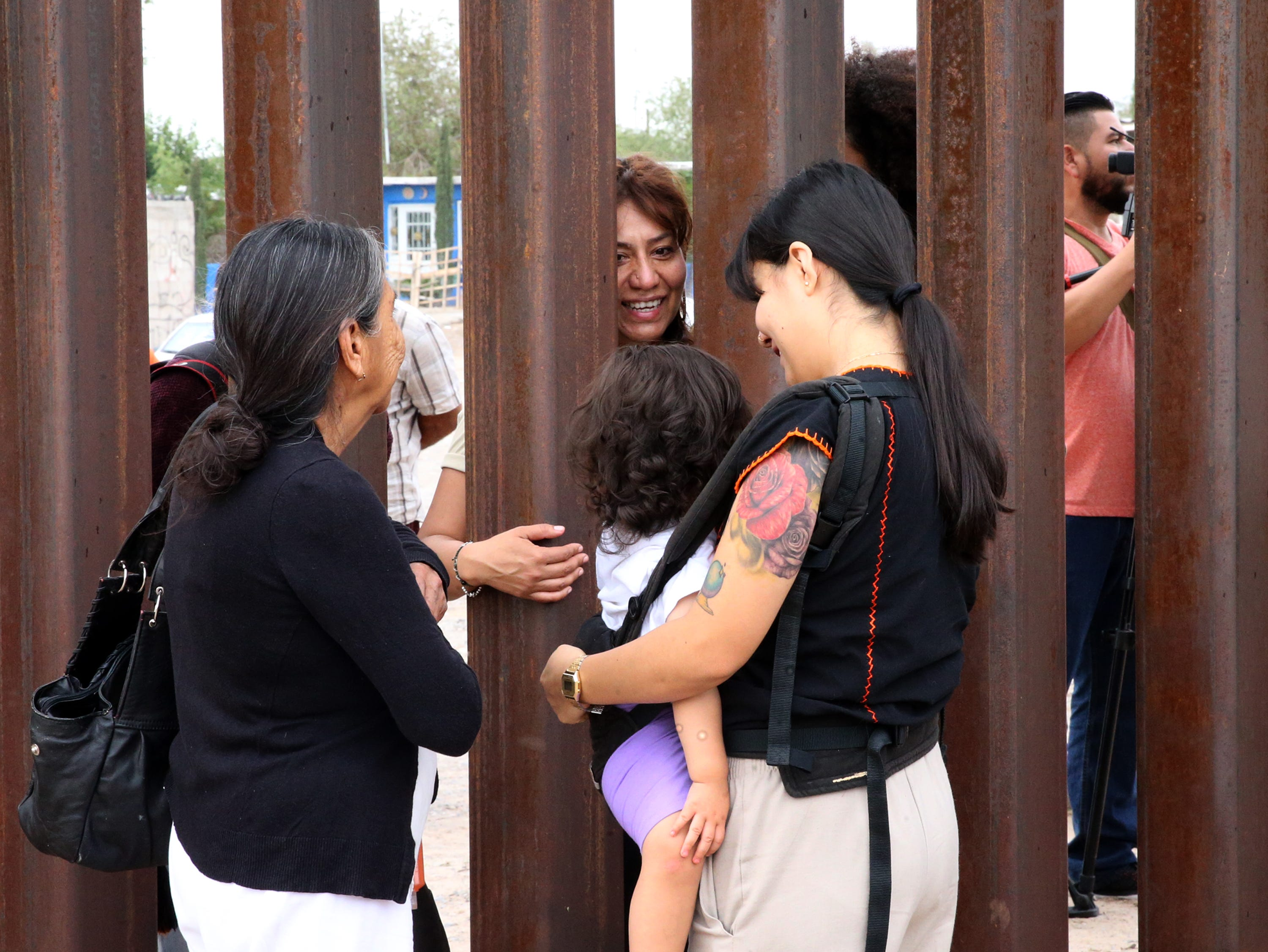 A family visits on the border fence in Sunland Park, N.M. Friday.