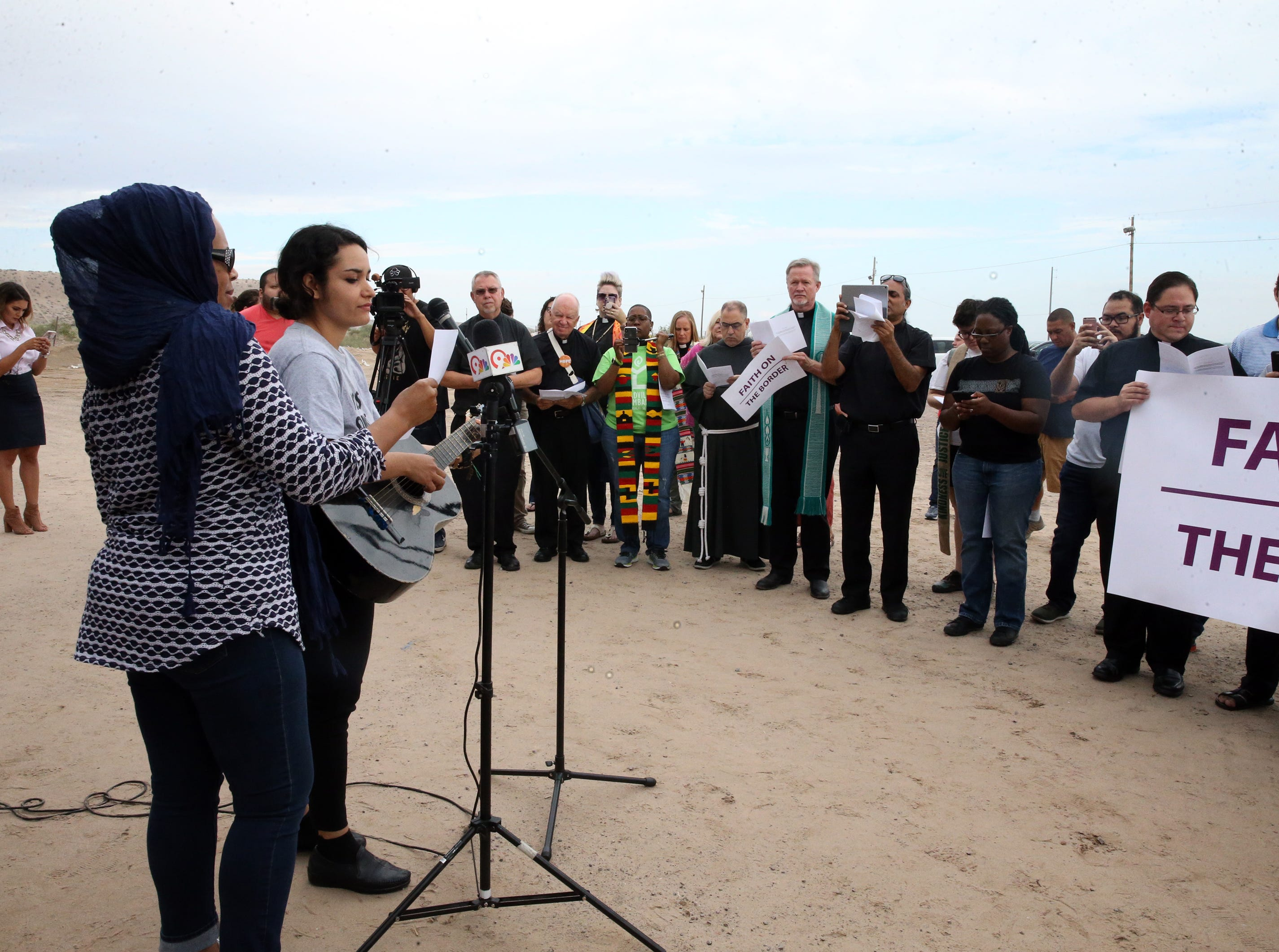 An interfaith group on both sides of the border fence listen to music Friday.