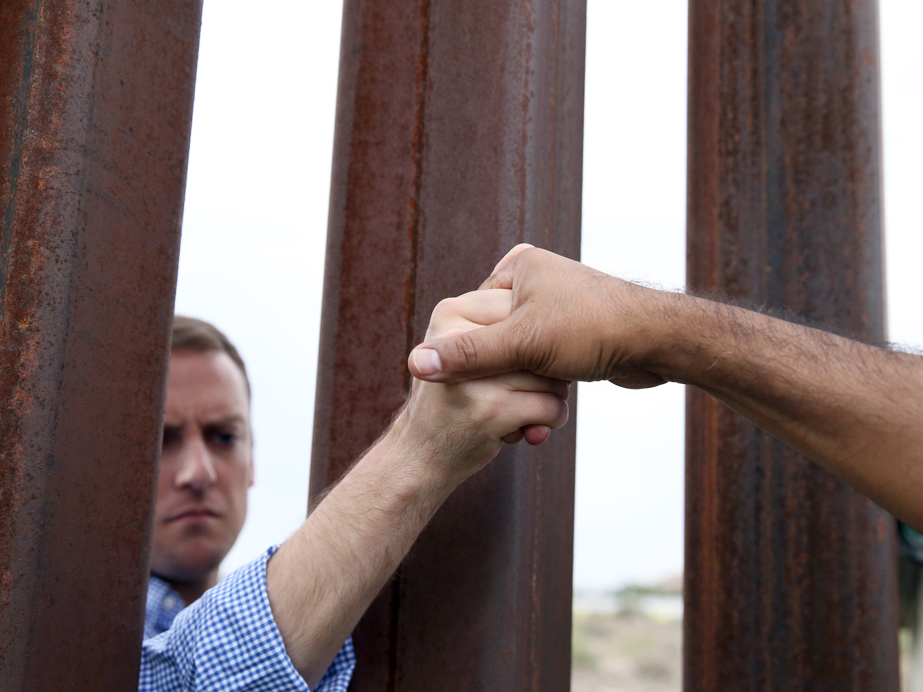 People gathered on both sides of the border shake hands through the border fence at Sunland Park, N.M. during an interfaith prayer vigil Friday.
