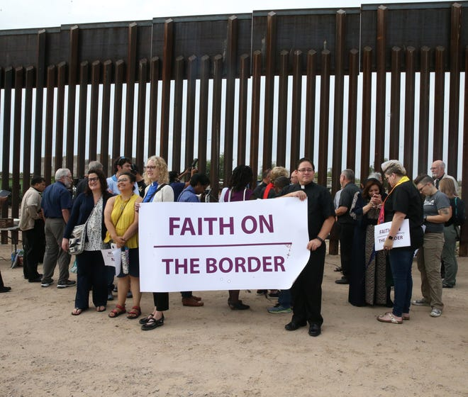 Members of an interfaith group representing three delegations pose Friday in front of the border fence in Sunland Park, N.M.