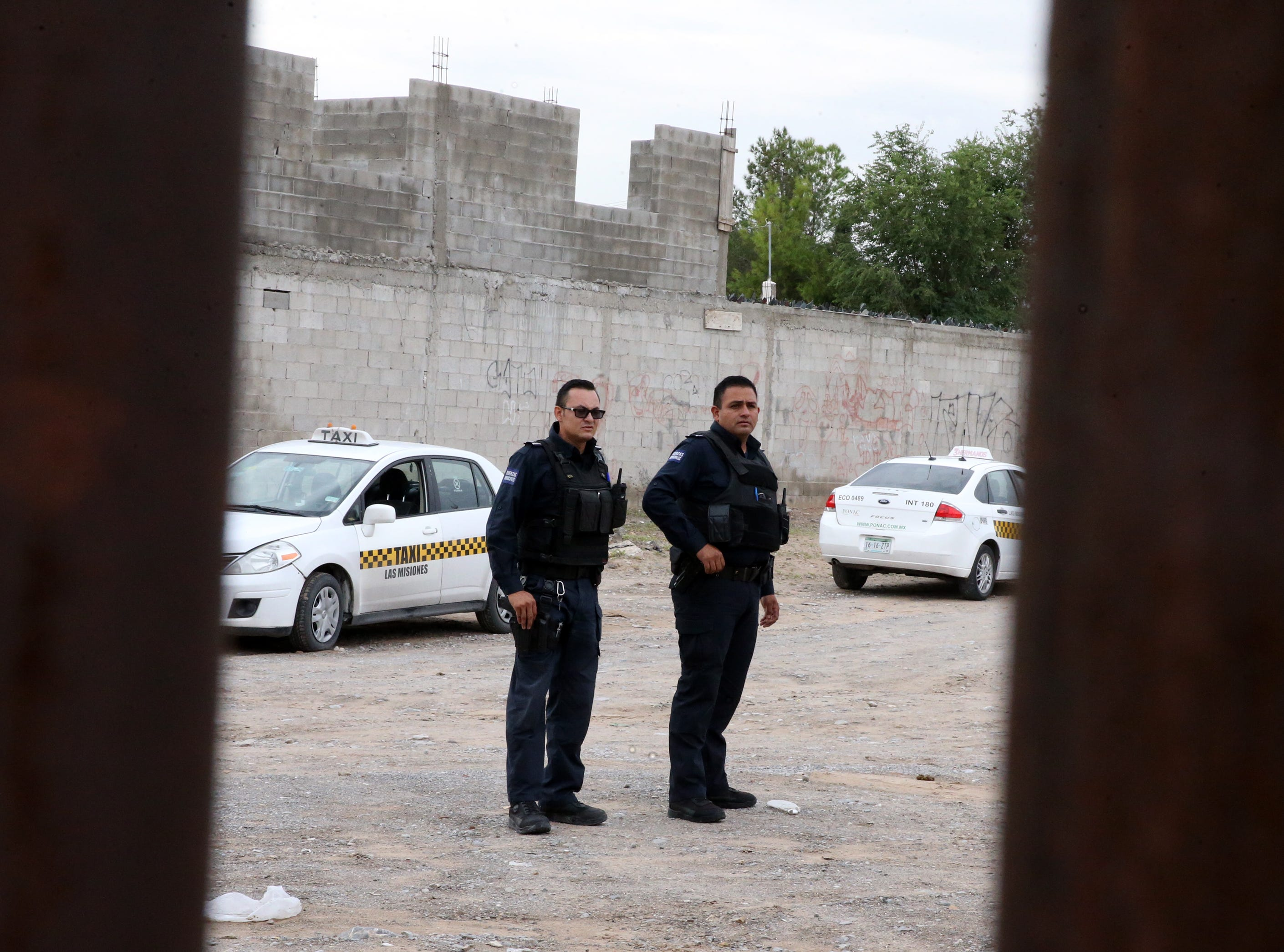 Juarez municipal police officers watch a gathering of people at the border fence in the Anapra area of Juarez Friday.