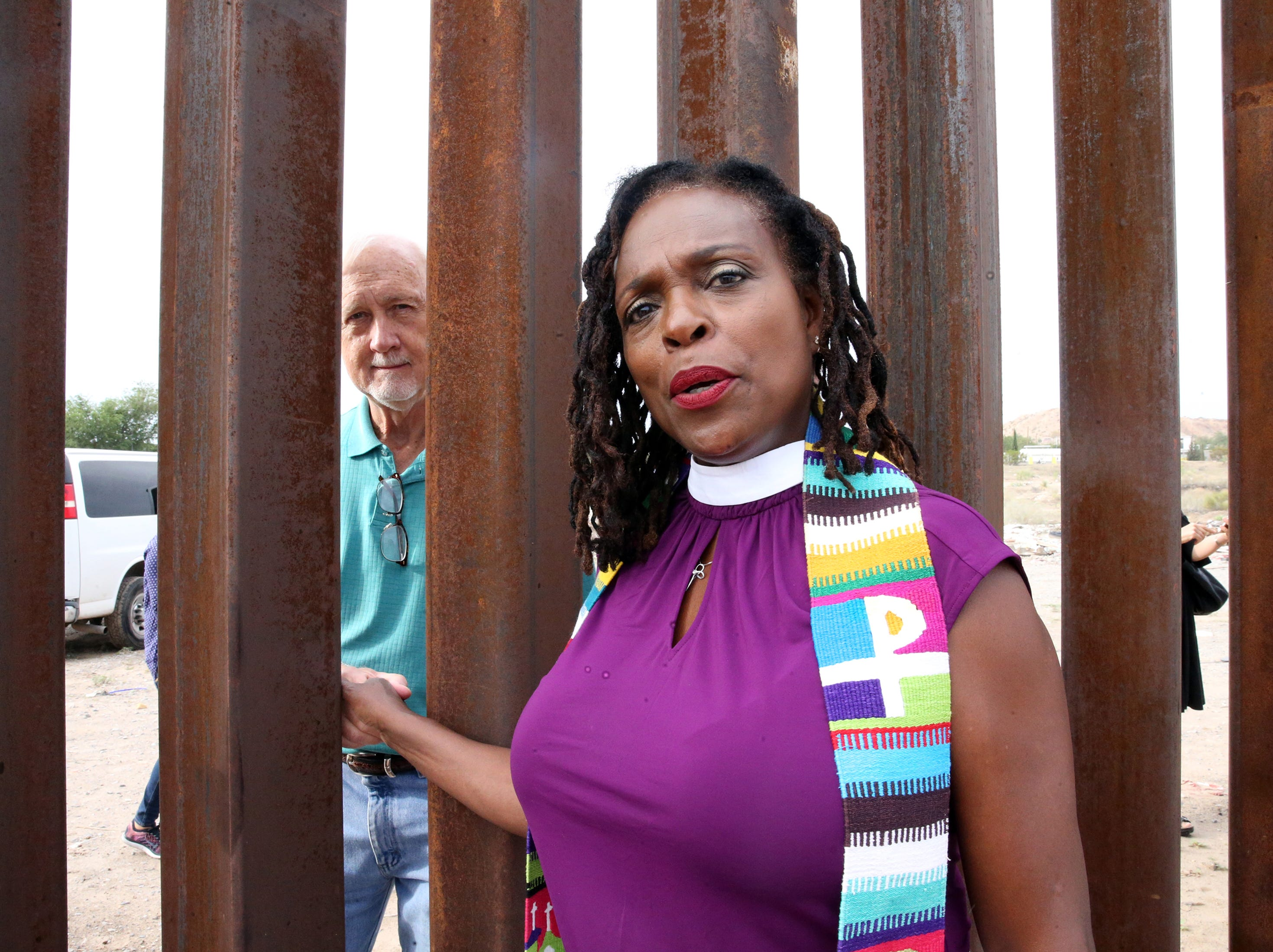 The Rev. Jacqui Lewis of Middle Church in New York City holds hands through the border fence with her husband, the Rev. John Janka of United Methodist Church, also in New York City, on Friday in Sunland Park, N.M.