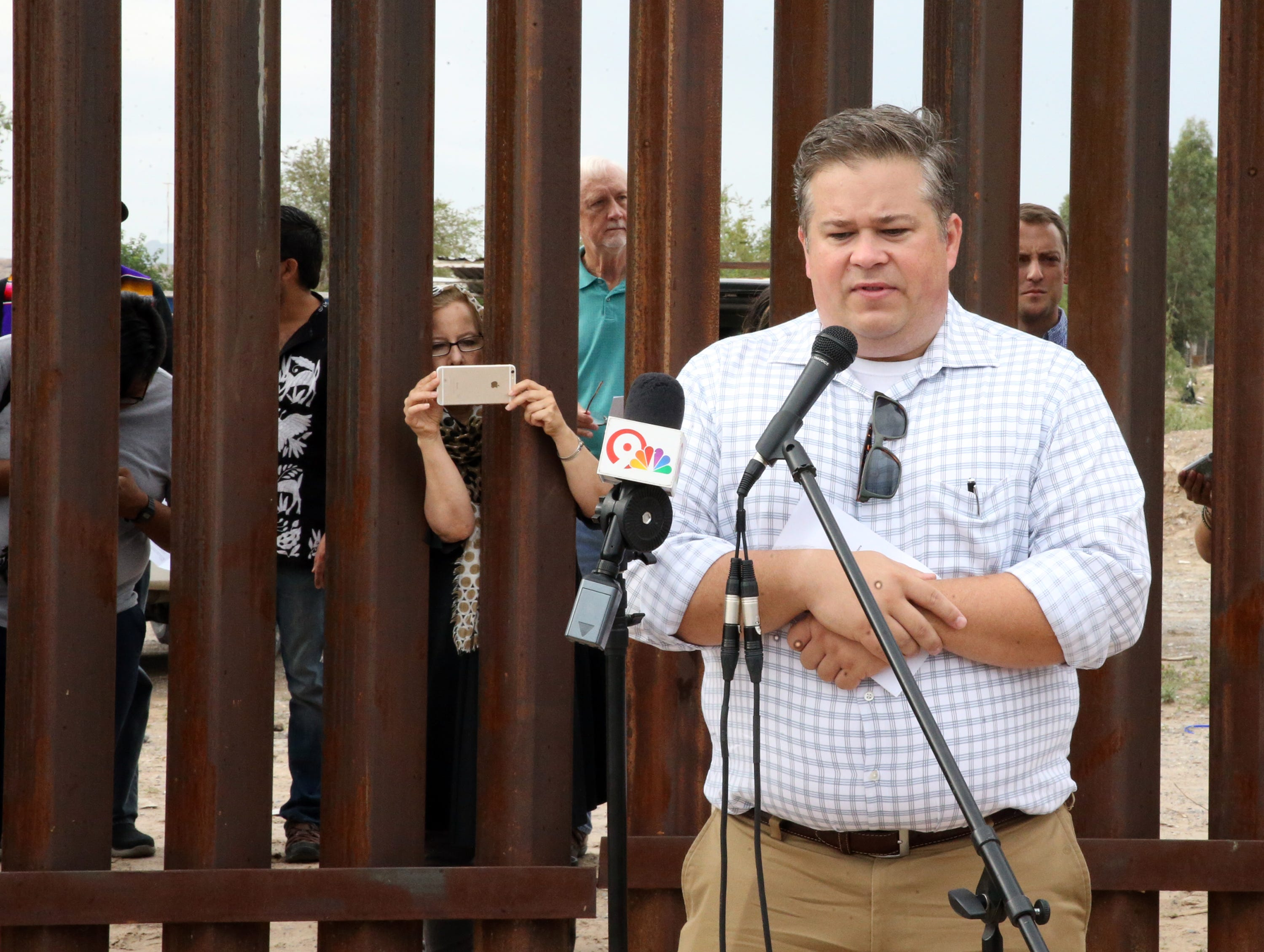 Dylan Corbett, executive director of Hope Border Institute speaks to a gathering of interfaith clergy at the border fence at Sunland Park, N.M. Friday.