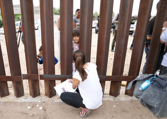 Allison Duber, bottom, of Cleveland, Ohio, talks with Brenda Alejandra Hernandez, 7, of the Anapra area of Juárez, on Friday at the border fence in Sunland Park, N.M. Duber is spending three months in the El Paso area.
